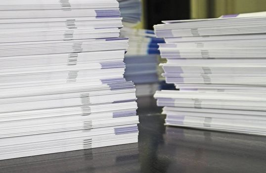 Piles of handout papers lying on a table.