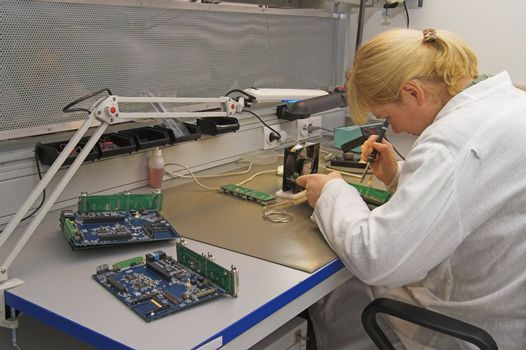 Engineer working with circuits - A woman engineer solders circuits sitting at a table.