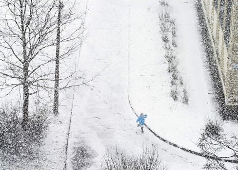 Girl running on road while snowfalling