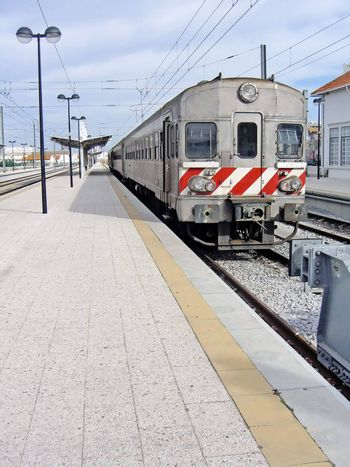 View of a portuguese train stopped at a train station.