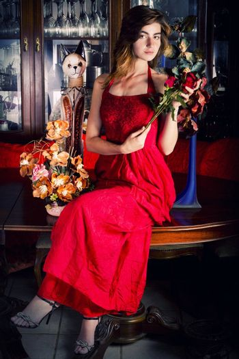 View of a beautiful young girl in a red dress on a living room.