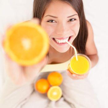 Orange juice drinking woman