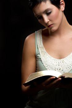 Beautiful young woman reading bible