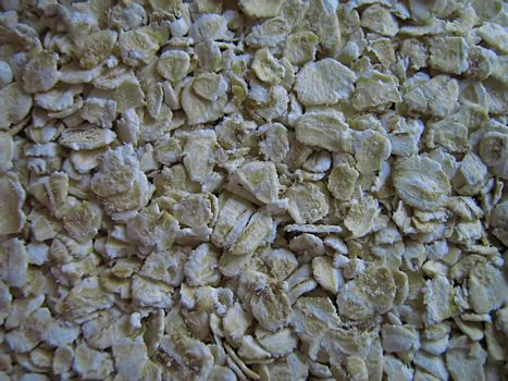A photograph of uncooked oatmeal detailing its texture.