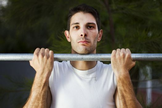 Close view of a young man doing exercise on a park.