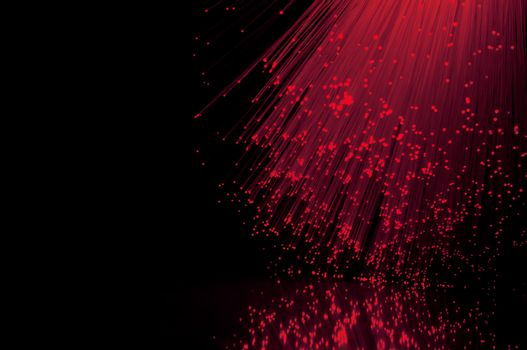 Crimson fiber optic light strands against a black background and reflecting into the foreground.