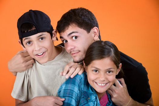 Teen holding and playing with brother and sister on an orange background
