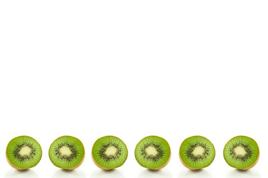 Six small kiwi fruit halves arranged in a horizontal line along the bottom of the image and over white.