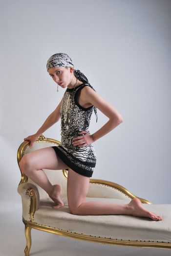 Woman kneeling on chaise lounge