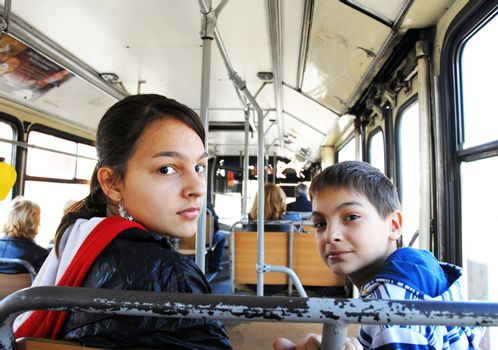 teenage girl and boy portrait looking over shoulder in city bus