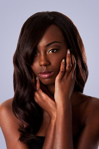 Beautiful face of an attractive African black woman with almond shaped eyes and long wavy hair and hands in her face, isolated.