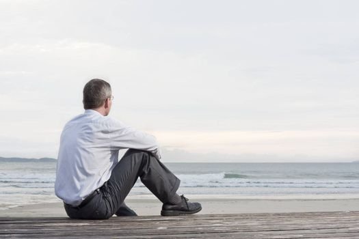 Pensive businessman sitting at the sea