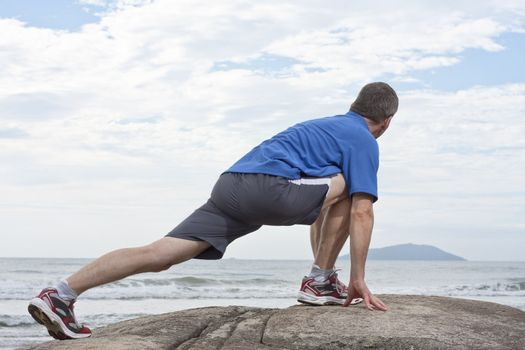 Runner doing stretching exercise on a rock at the sea