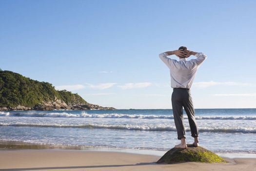Businessman standing on a rock at the sea
