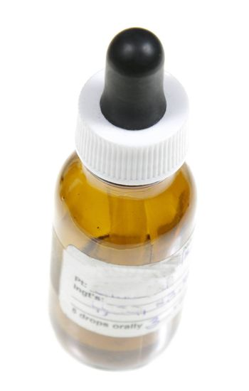 A dropper bottle containing naturopathic medicine, isolated on a white background.