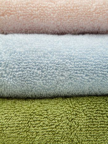 Stack of three bath towels of different colors