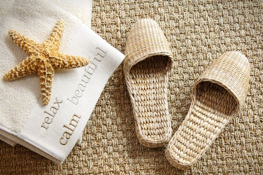 Spa slippers on seagrass carpet with towels