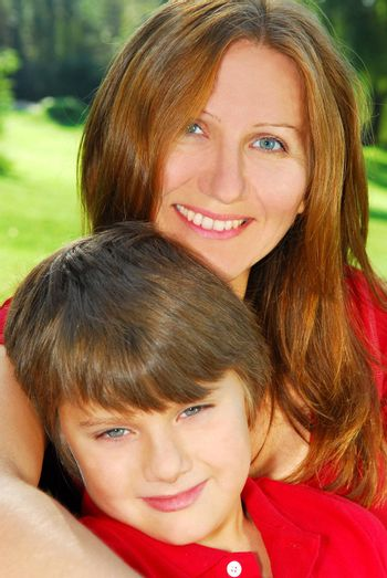Portrait of smiling mother and son in summer park