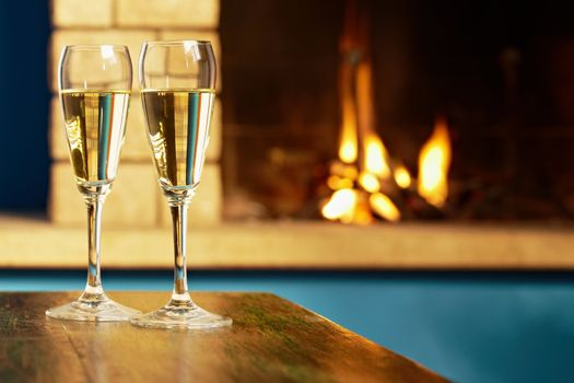 two flutes filled with champagne near fireplace