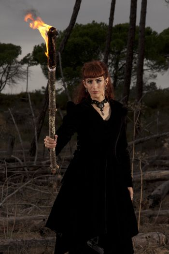 View of a dark clothed woman with a torch on her hands.