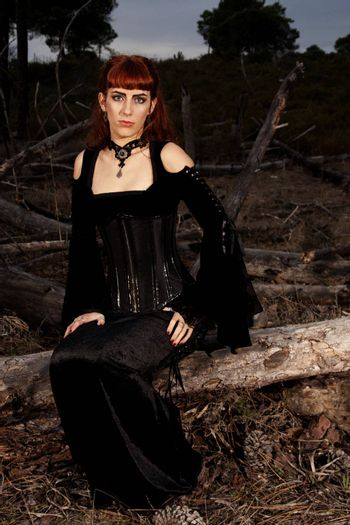 Dark gothic woman with dark clothes posing on the night forest.