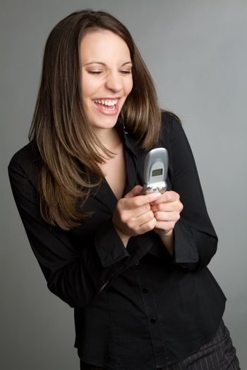 Laughing woman texting on phone