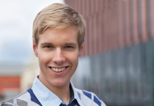 Handsome blond young man smiling outdoors; blurred background