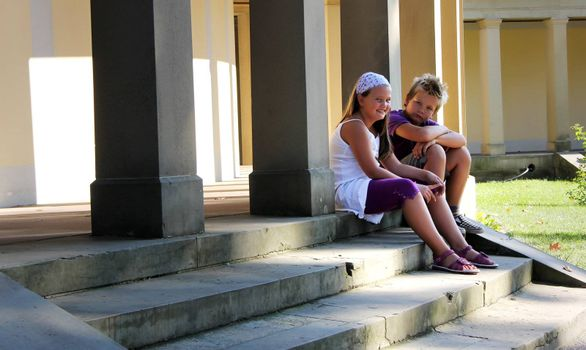 two childrens are sitting in front of an old pathway with pillars