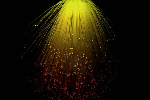 Yello and red coloured fibre optic light strands cascading down with a black background.