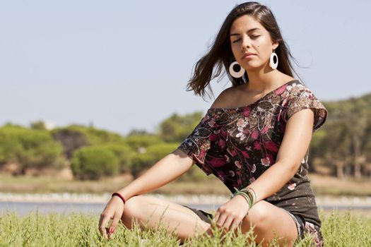 Beautiful girl with floral dress meditating on the nature.