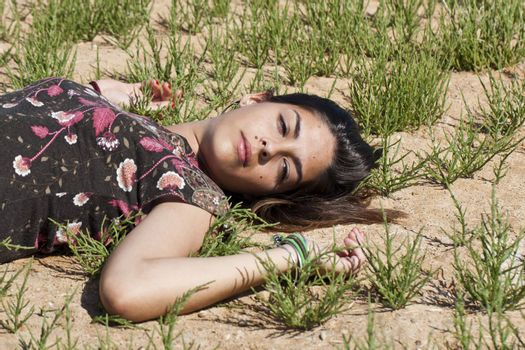 Beautiful girl with floral dress sleeping on the nature.