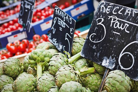 Closeup view on farm market counter with artichokes on the foreground; price tags in French