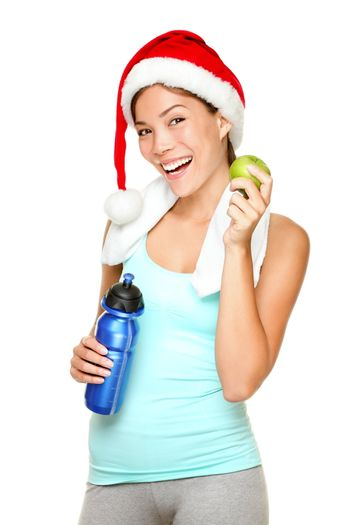 Christmas fitness sport woman wearing santa hat eating apple. Mixed race Chinese Asian Caucasian female fitness model isolated on white background.