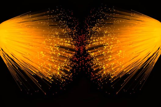 Two illuminated groups of vibrant gold fibre optic strands emanating from the left and right of the image. Black background.
