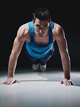 Man doing push-ups on black background