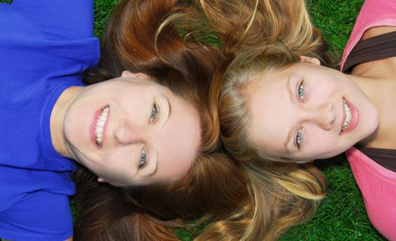 Portrait of smiling family of mother and her teenage daughter lying on grass in summer park