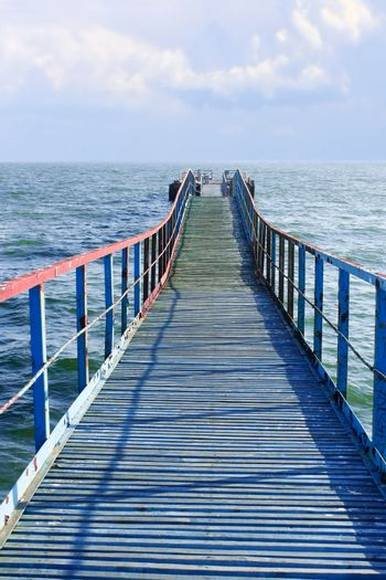Old wooden sea pier that goes away