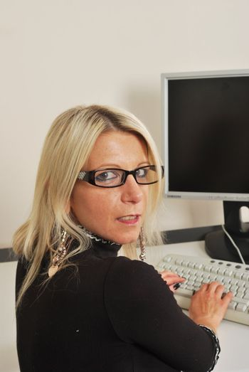 Business woman with glasses sitting at keyboard looking at camera