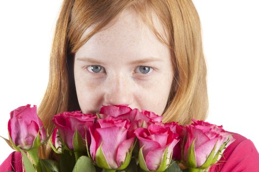 young girl is smelling at beautiful pink roses on a white backgr