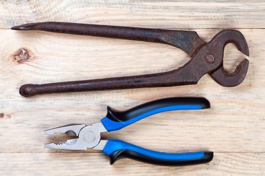 Pliers and tongs on wooden background.