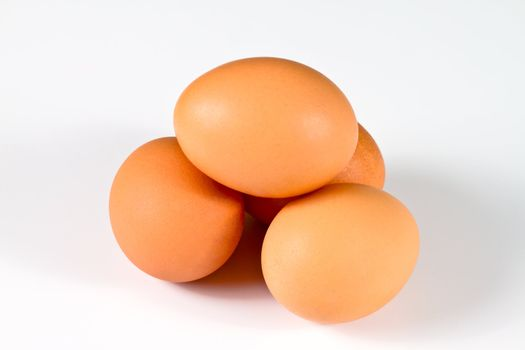 Four brown eggs arranged as a dolmen, isolated on white background