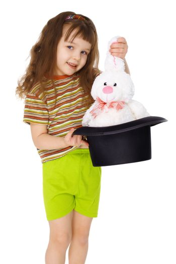 A child gets a rabbit out of a hat like a magician isolated on white background