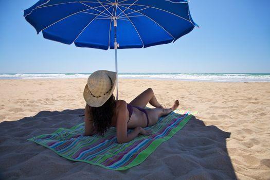 woman lie down under parasol