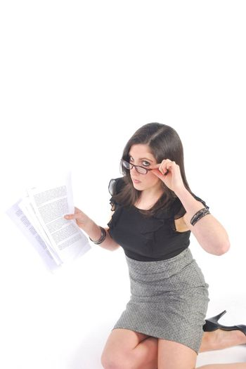 Business woman kneeling reading papers
