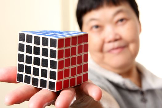senior chinese woman show a complete  rubik cube