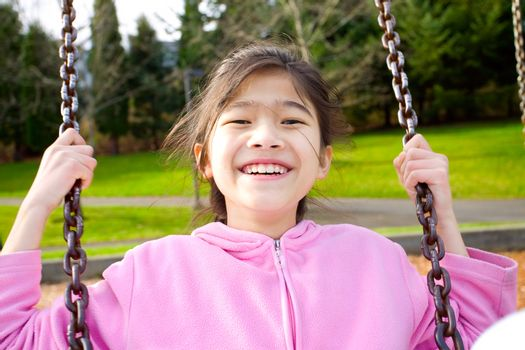 Happy little girl smiling on a swing at the park