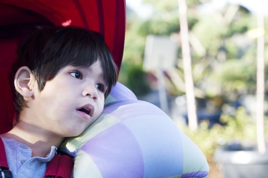 Cute four year old boy looking quietly off to side