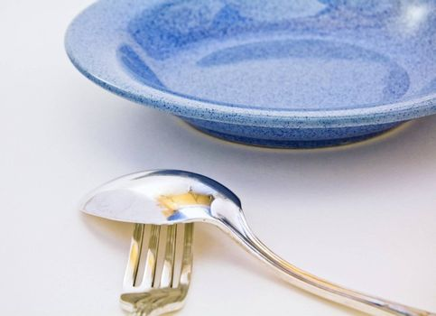 spoon on fork and blue plate