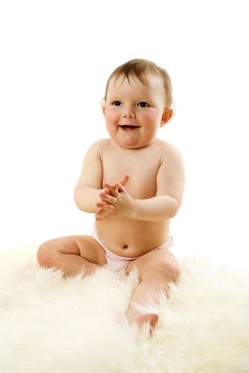 Baby sitting on fur laughing isolated on white