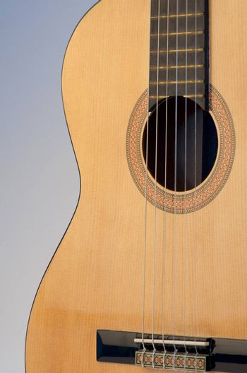 High resolution image.  Classical acoustic guitar, isolated on grey background.